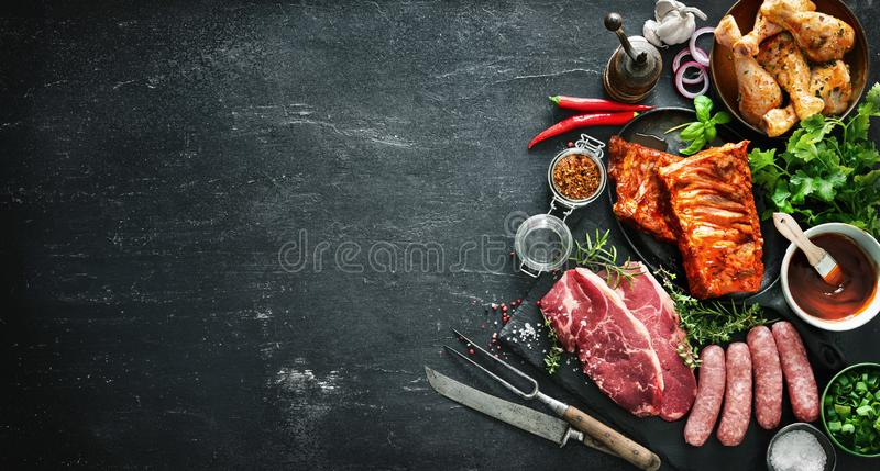 Various kinds of grill and bbq meats with vintage kitchen and butcher utensils. Chicken legs, steaks, sausages, pork ribs with herbs, spices, sauces and royalty free stock photography