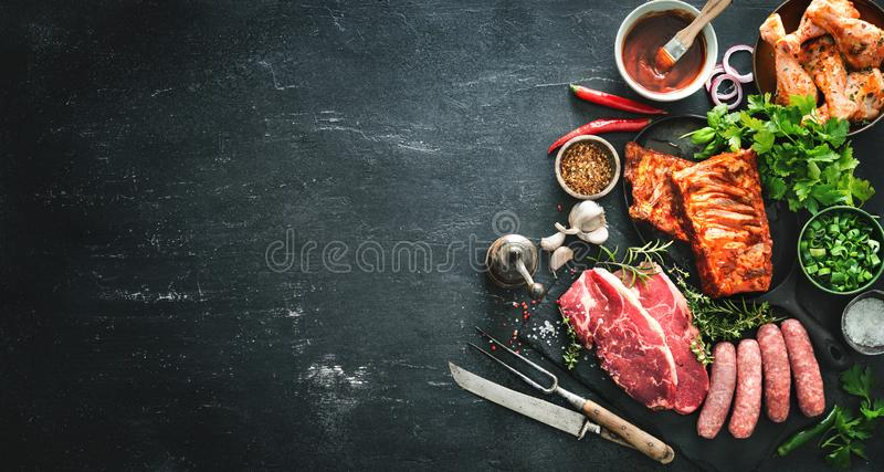 Various kinds of grill and bbq meats with vintage kitchen and butcher utensils royalty free stock image