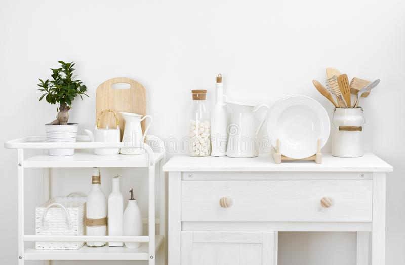 Various kitchen utensils and dishware with elegant vintage white furniture.  stock photo