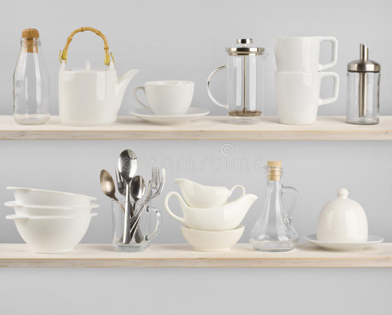 Various kitchen utensils on wooden shelves stock photography