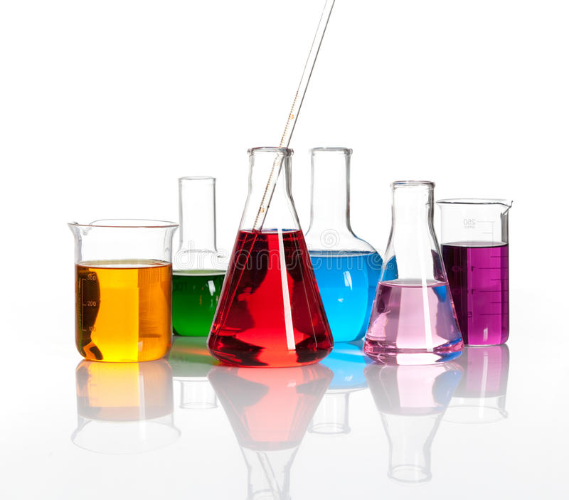 Various laboratory flasks with a colored liqiuds. Various laboratory flasks with a colored reagents, isolated royalty free stock images