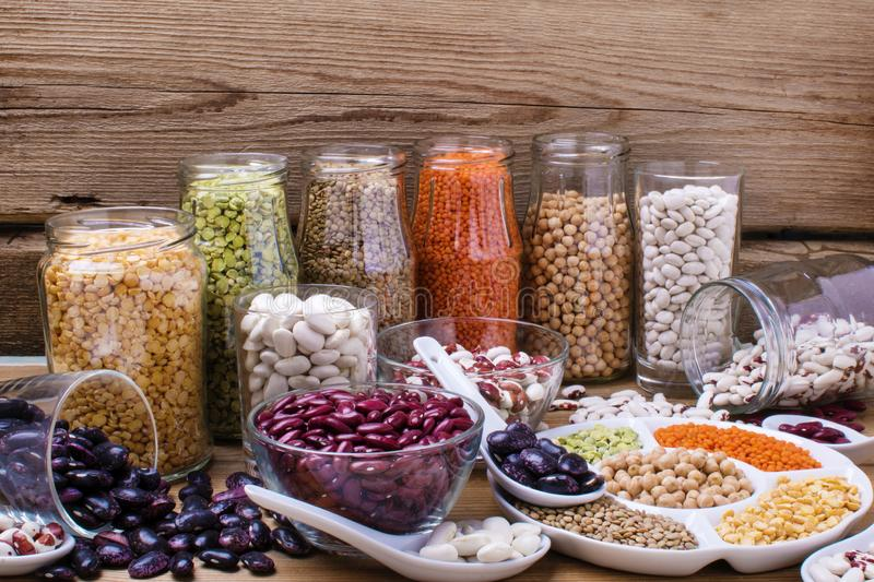 Various legumes: beans, chickpeas, lentils in glass jars on wooden background. Healthy vegetarian food stock photos