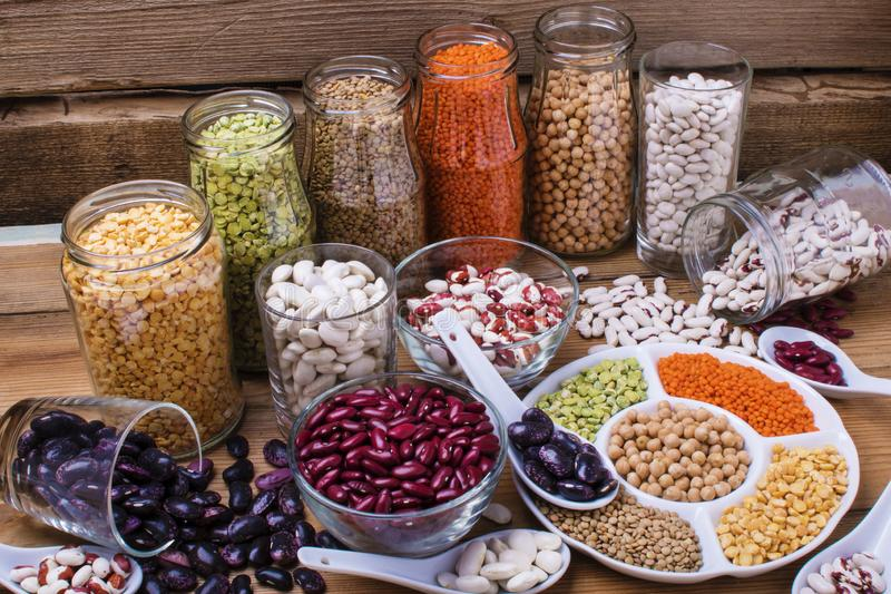 Various legumes in different bowls. Vegan protein source. Legumes - lentils, chickpeas, beans, red bean on wooden background royalty free stock photo