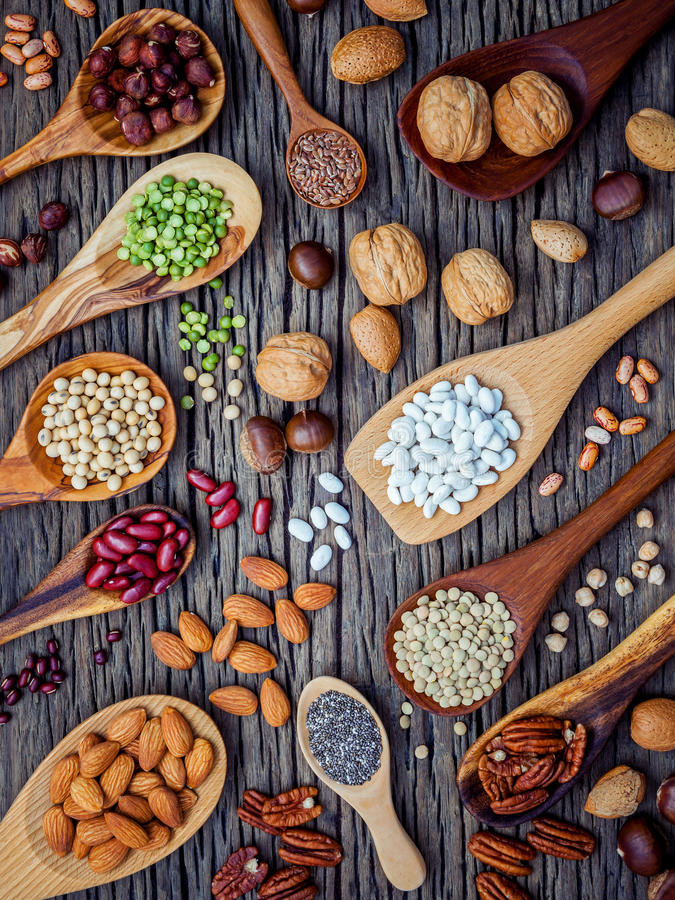 Various legumes and different kinds of nutshells in spoons. Walnuts kernels ,hazelnuts, almond ,brown pinto ,soy beans ,flax seed royalty free stock images
