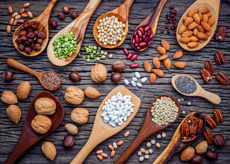 Various legumes and different kinds of nutshells in spoons. Walnuts kernels ,hazelnuts, almond ,brown pinto ,soy beans ,flax seed stock images