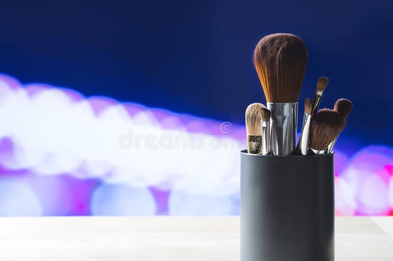 Various make up brushes in container on table stock photos