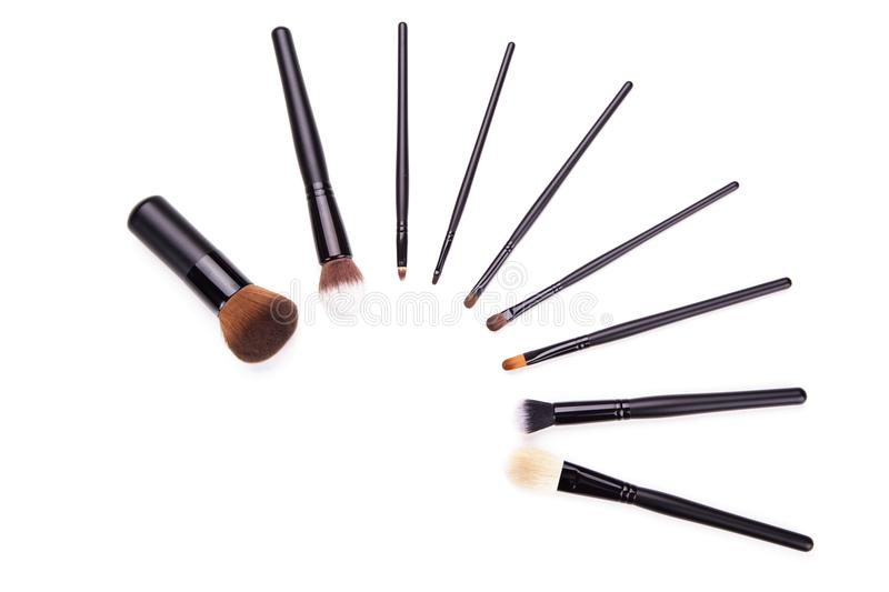 Various makeup brushes isolated over white background,Flat top view set of essential professional make-up brushes on white backgro stock image