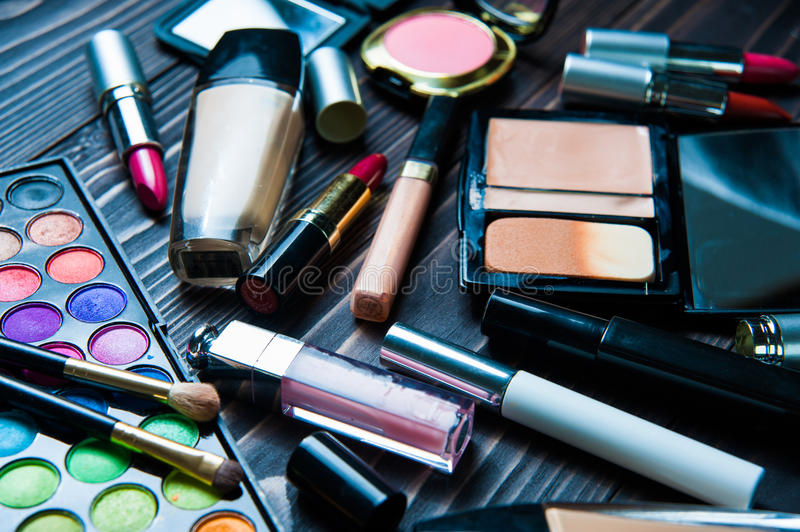 Various makeup products on dark background. Cosmetics make up artist objects: lipstick, eye shadows, eyeliner, concealer. Tools for make-up royalty free stock image
