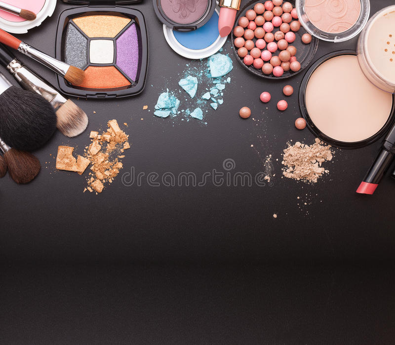Various makeup products on dark black background with copyspace royalty free stock images