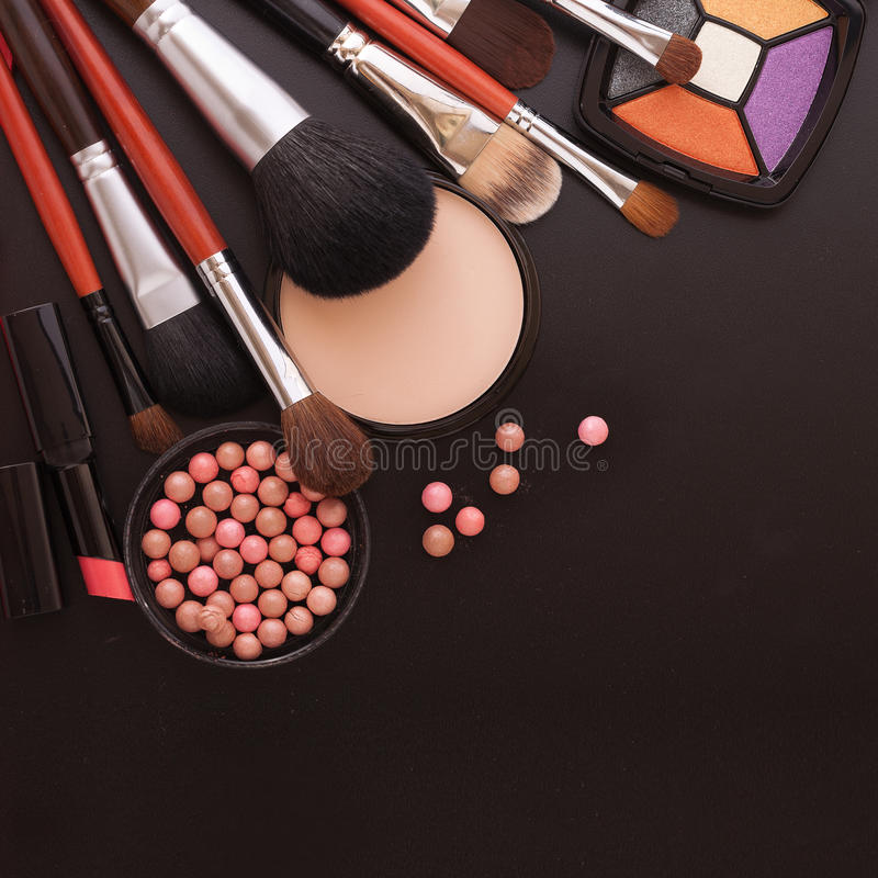 Various makeup products on dark black background with copyspace stock image