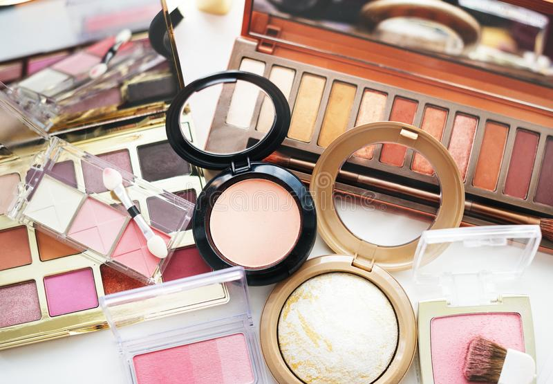 Various makeup products on white table stock photography