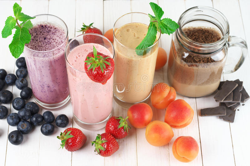 Various milkshakes with fruits. Various fruit and chocolate protein milkshakes in glasses on rustic white wooden background. Overhead view royalty free stock photos
