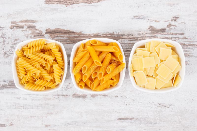 Various mix pasta in bowls as source carbohydrates and fiber stock photo