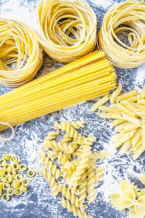 Various mix of pasta on a gray concrete background. Diet and food concept. stock photo