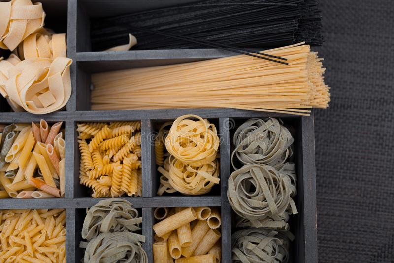 Various mix of pasta on wooden rustic background, wood desk and wooden box. royalty free stock images