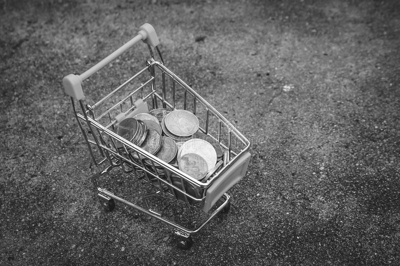 Various money coins Baht in yellow mini shopping cart or supermarket trolley set on concrete floor in black and white image. royalty free stock images