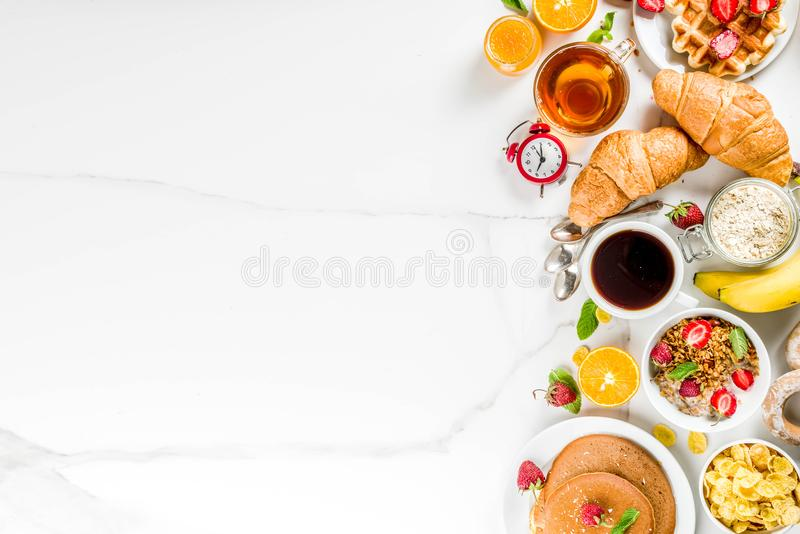 Various morning breakfast food. Healthy breakfast eating concept, various morning food - pancakes, waffles, croissant oatmeal sandwich and granola with yogurt stock image