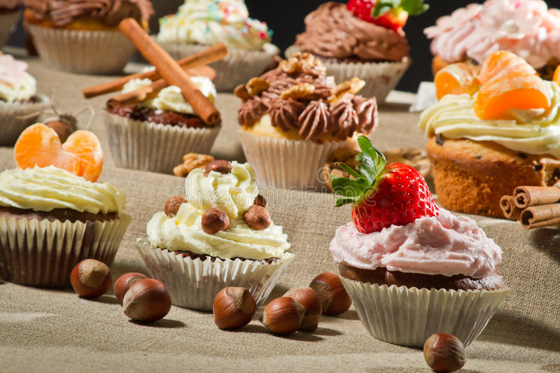 Various muffin with cream and fruits stock image