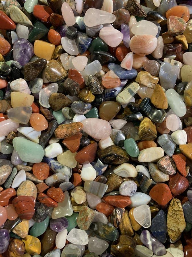 Various multi-colored gems. Tigers eye, amethyst, rose quartz, aventurine, jadeite, topaz, black opal, moonstone. Background stock photo