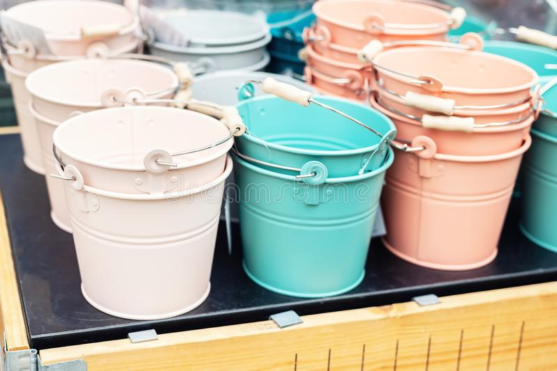 Various multicolored bright small ornamental metal buckets for sale on wooden table outdoors. Many colorful decorative mini pails. For garden flower plants stock images