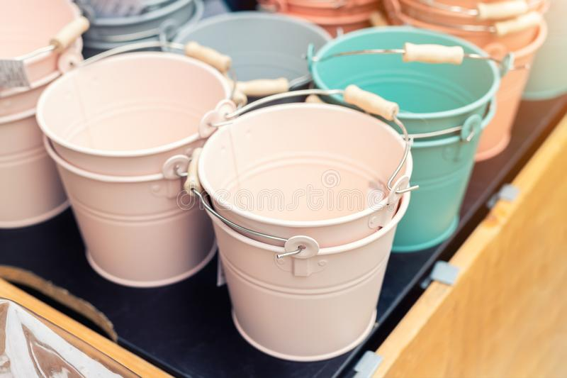 Various multicolored bright small ornamental metal buckets for sale on wooden table outdoors. Many colorful decorative mini pails. For garden flower plants royalty free stock photos