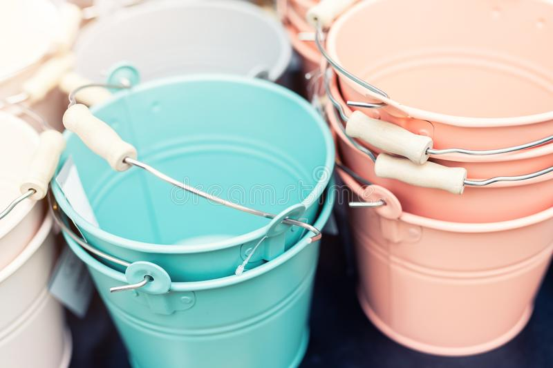 Various multicolored bright small ornamental metal buckets for sale on wooden table outdoors. Many colorful decorative mini pails. For garden flower plants royalty free stock images