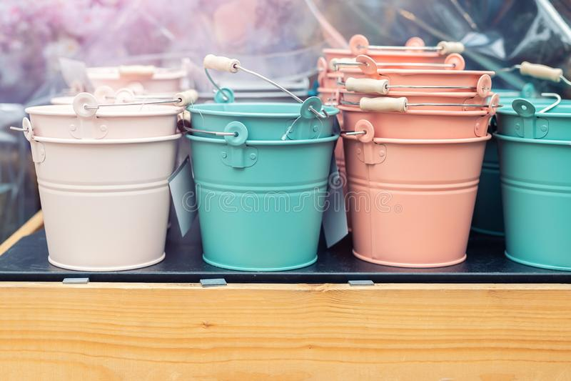 Various multicolored bright small ornamental metal buckets for sale on wooden table outdoors. Many colorful decorative mini pails. For garden flower plants royalty free stock photo
