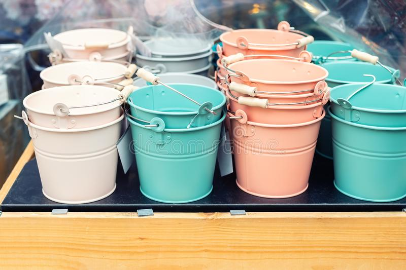 Various multicolored bright small ornamental metal buckets for sale on wooden table outdoors. Many colorful decorative mini pails. For garden flower plants stock image