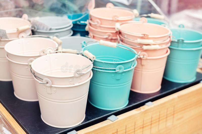 Various multicolored bright small ornamental metal buckets for sale on wooden table outdoors. Many colorful decorative mini pails. For garden flower plants stock photo