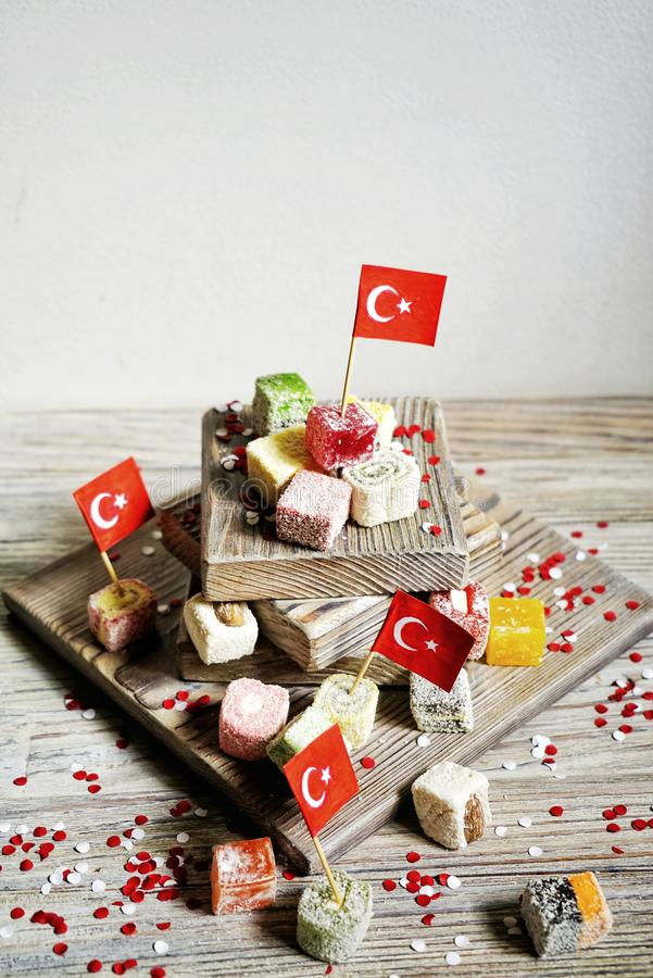 Various national Oriental sweets, with paper flags of Turkey, Turkish delight on a wooden white brushed stand and on a white brush. Ed background, vertical, the royalty free stock image