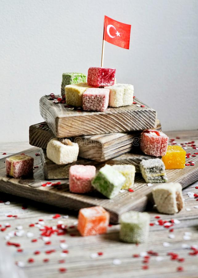Various national Oriental sweets, with paper flags of Turkey, Turkish delight on a wooden white brushed stand and on a white brush. Ed background, vertical, the royalty free stock photo