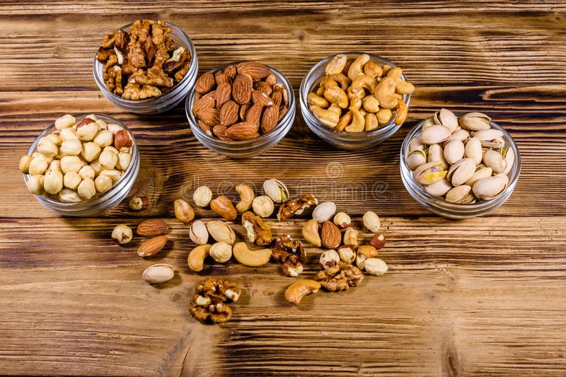 Various nuts almond, cashew, hazelnut, pistachio, walnut in glass bowls on a wooden table. Vegetarian meal. Healthy eating stock photos