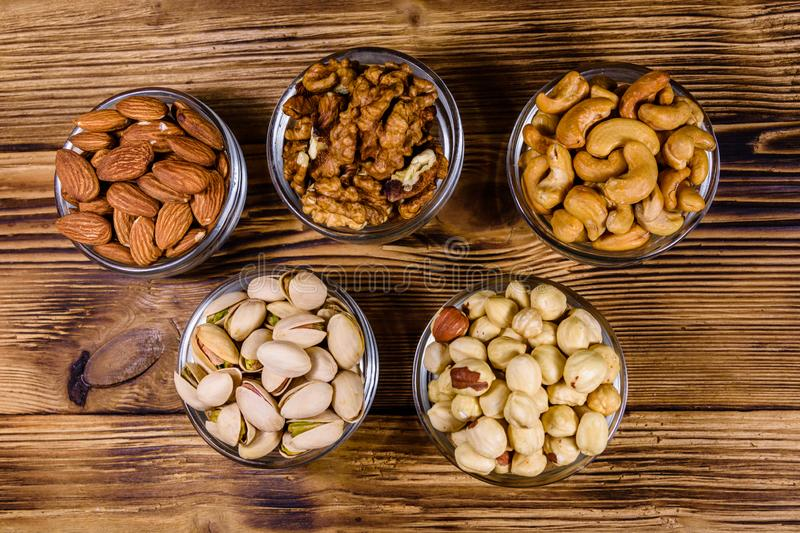 Various nuts almond, cashew, hazelnut, pistachio, walnut in glass bowls on a wooden table. Vegetarian meal. Healthy eating royalty free stock photo
