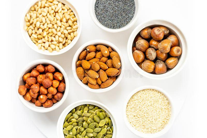 Various Nuts and Seeds on White Background in the Bowls with Free Space for Text. Various Nuts and Seeds on White Background in the Bowls royalty free stock image