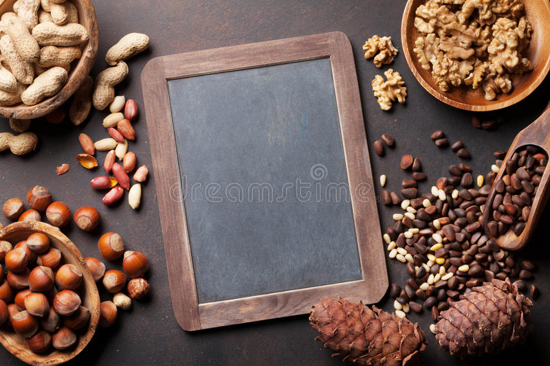 Various nuts on stone table royalty free stock images