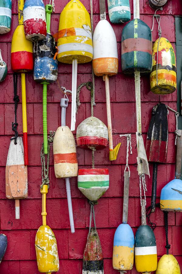 Various onboard used floats for mooring boats and schooners are decoratively hung on the wall of the building. Different sized board side floats for safe soft royalty free stock image