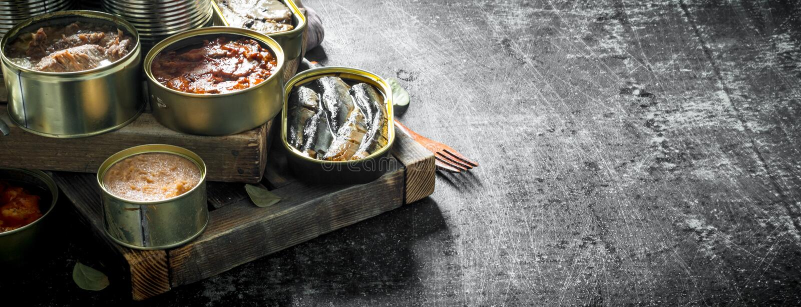 Various open tin cans with canned food on wooden tray. On dark rustic background stock photo