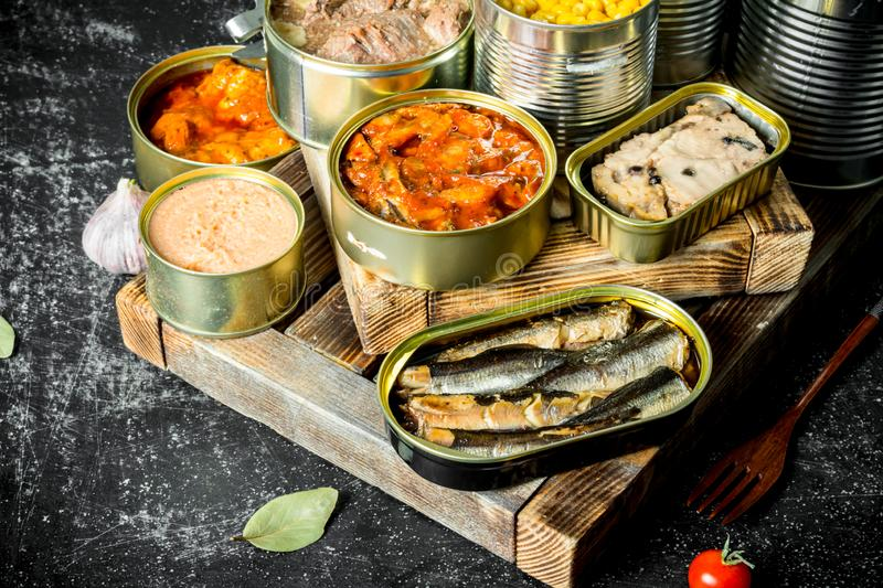 Various open tin cans with canned food on wooden tray. On dark rustic background stock images