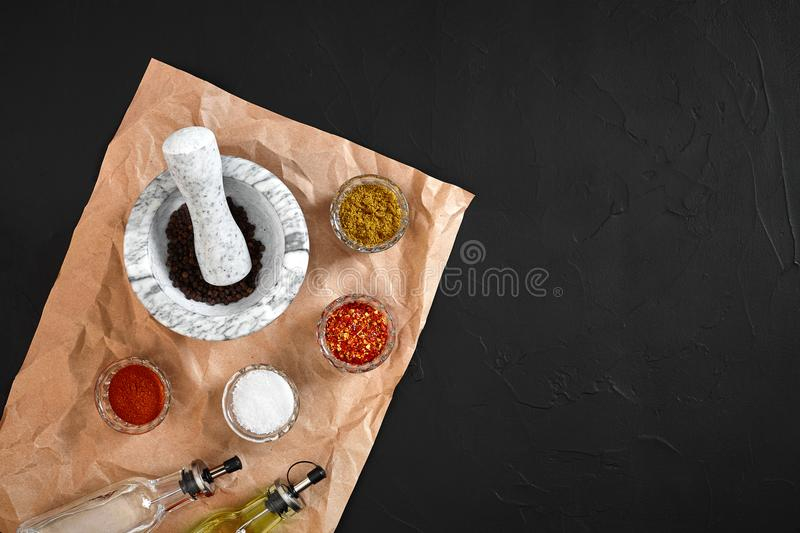 Various spices and mortar on black background with copy space royalty free stock photos