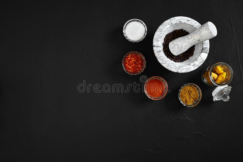 Various spices and mortar on black background with copy space stock photo