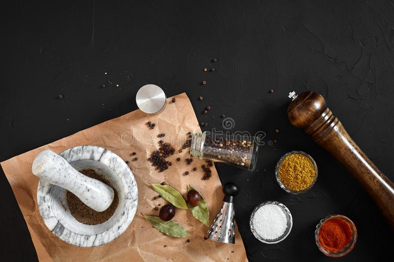 Various spices and mortar on black background with copy space stock photography