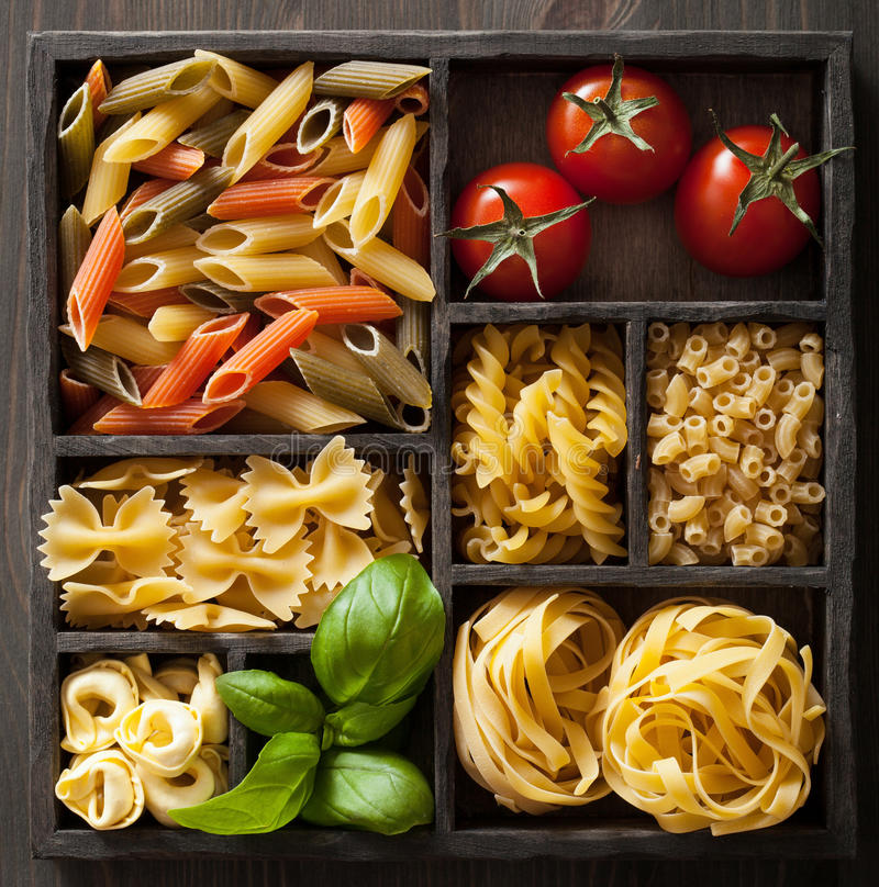Various pasta in black wooden box royalty free stock photo