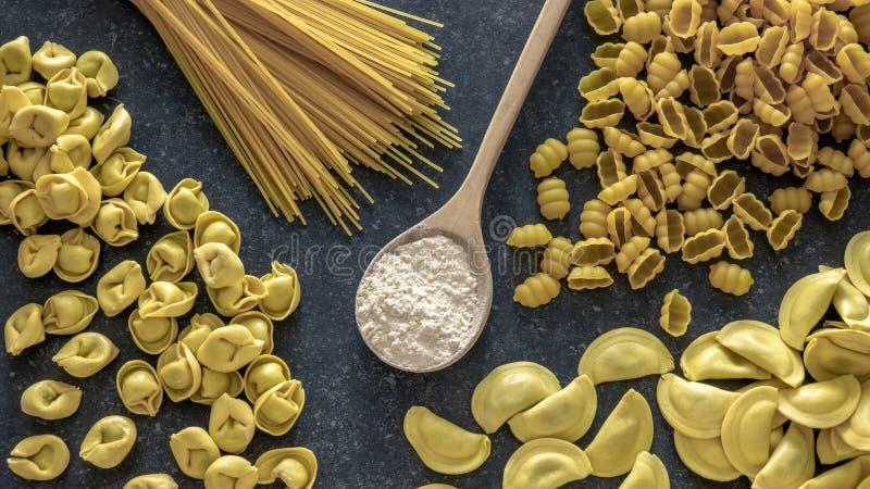 Various pasta and flour on dark stone background royalty free stock photos