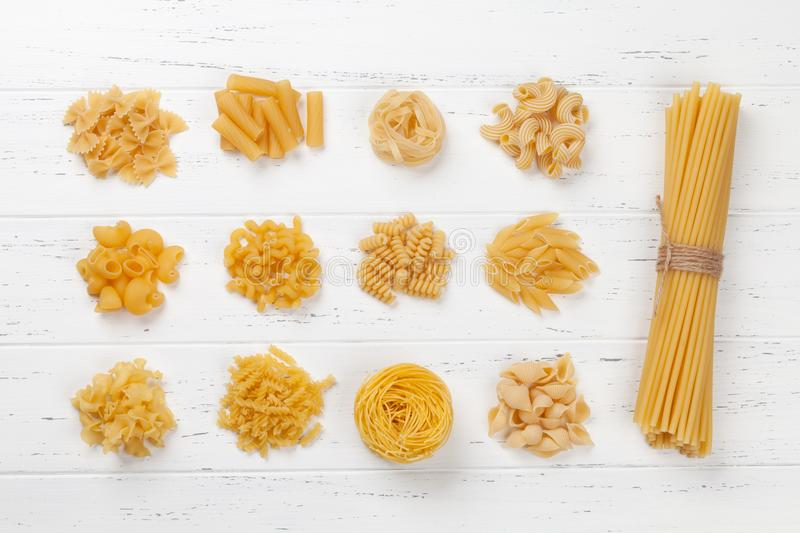 Various pasta on white wooden table royalty free stock image