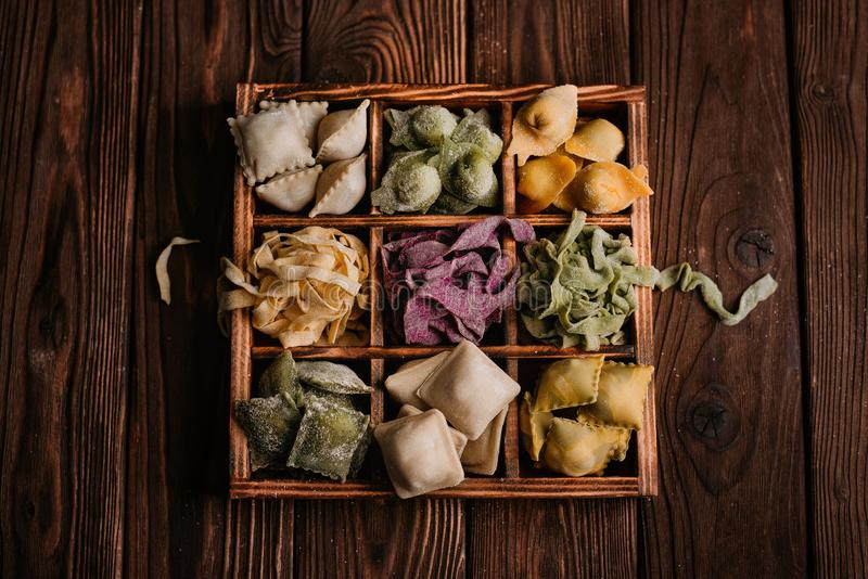 Various clorful pasta in wooden box royalty free stock images