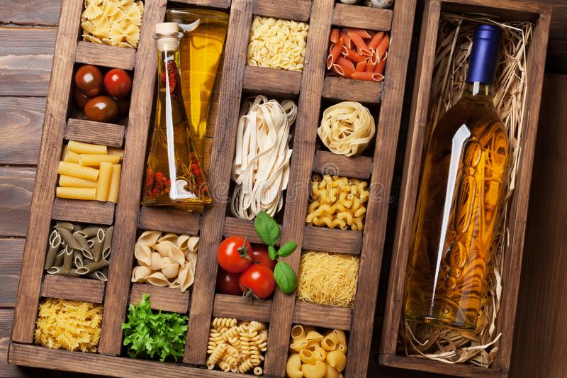 Various pasta in wooden box and wine stock image