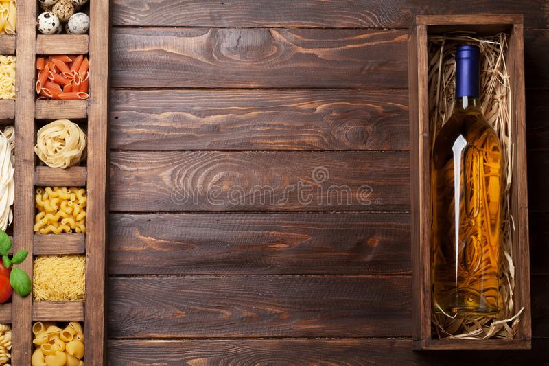 Various pasta in wooden box and wine royalty free stock photography