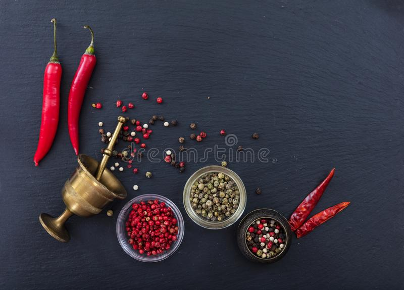 Variety of peppercorns and fresh and dried peppers on black background, top view, copy space stock photos