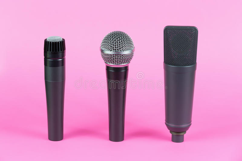 Various professional microphones on pink background. Mic stock image