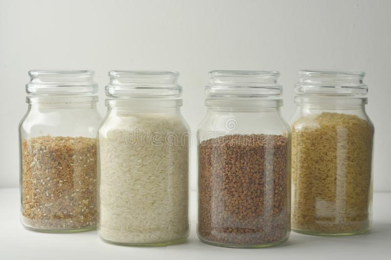 Various raw cereals, grains, rise, buckwheat and flakes. Healthy cooking in glass jars, white background. Clean eating royalty free stock image